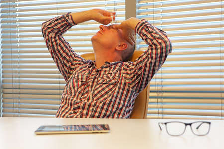 middle age caucasian man  applying eye drops  sitting at the desk in office Stock Photo