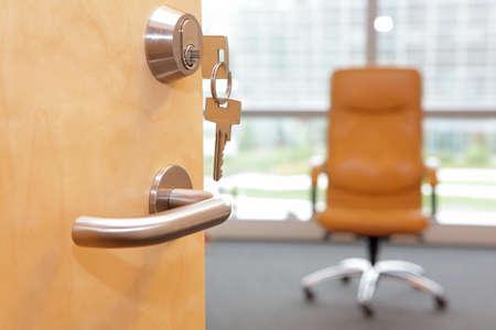 Vacature job. Half geopende deur naar een office.Door handvat, deurslot, leunstoel op wielen inside - onscherp Stockfoto