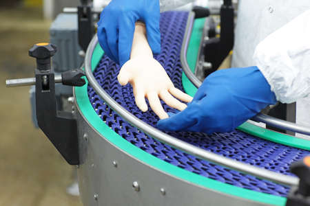 technician at conveyor belt controlling artificial bionic hand . a concept of spare body parts