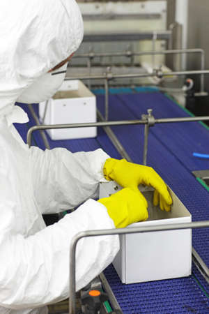 obrero trabajando: trabajador en la máscara uniforme de protección, guantes de trabajo con las cajas en línea en línea de envasado en la fábrica Foto de archivo