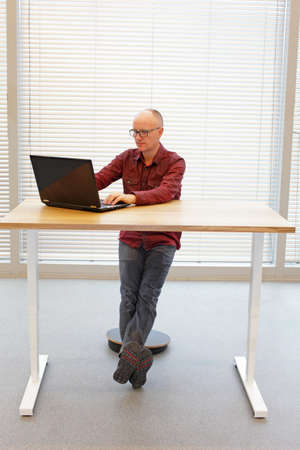 office desk: ergonomics in office work - man at the desk on pneumatic stool Stock Photo