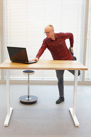 online: leg exercise during standing office work -  middle age balding man in eyeglasses man  with laptop at the mobile table Stock Photo
