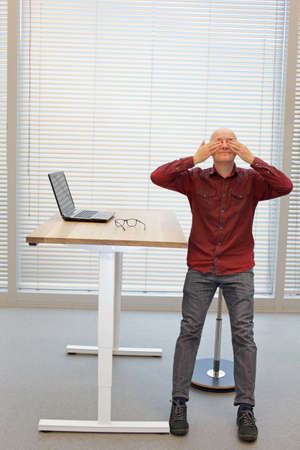middle age  practicing yoga for eyes in office - having  break