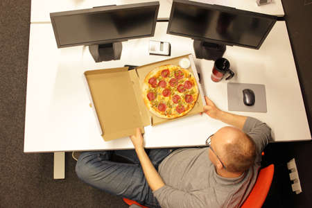 fast meal: fast meal in office - man heaving break for pizza