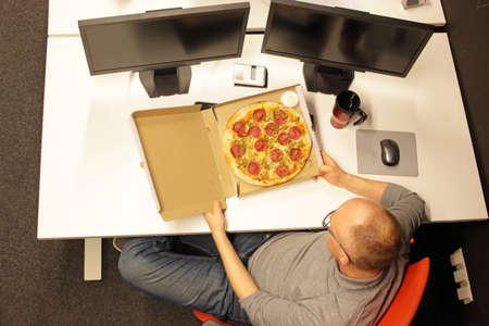fast meal in office - man heaving break for pizza