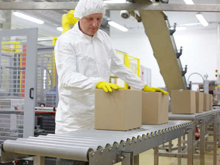 Manual worker in white uniform,cap and yellow gloves, at production line dealing with boxes Stock Photo