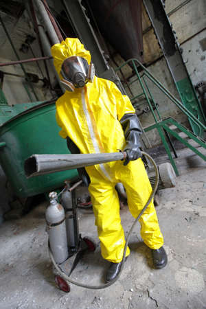 professional in protective uniform, mask, gloves with fire extinguisher in industrial building Stock Photo