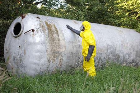 técnico en uniforme que examina gran tanque de acero photo
