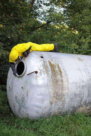 technician in uniform examining large stainless tank photo
