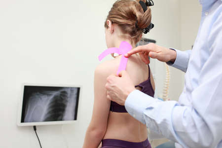 specialist performing  kinesio taping application on girls shoulder  in office