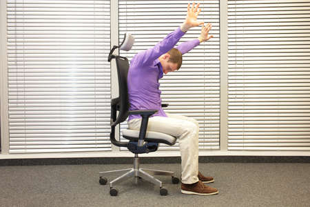 caucasian man stretching arms,exercising on chair in office, healthy lifestyle