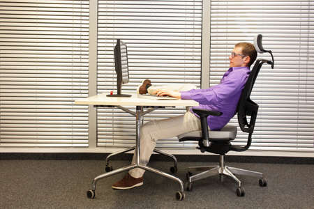 mobile: bad sitting position at workstation in office - man stretching leg Stock Photo