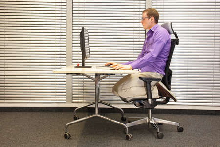 man in slouching position kneeling on ergonomic chair working with computer at desk -text neck