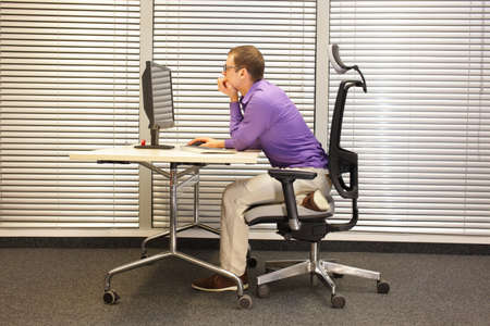 Near-sightedness, myopia. Caucasian office worker at work station stretching leg Stock Photo