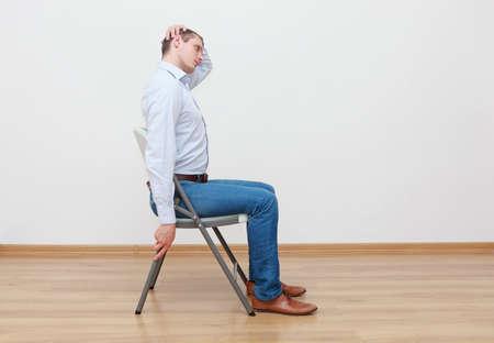 Homme de race blanche, assis sur une chaise, étirement du cou - profil