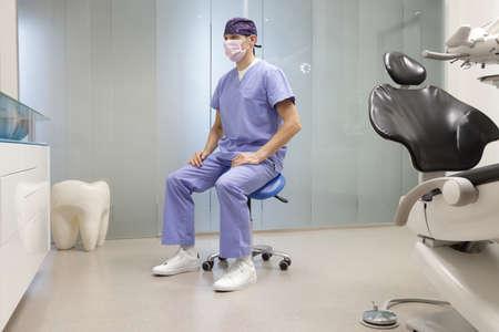 Dentista meditando en la posición correcta para sentarse en una silla en su oficina.