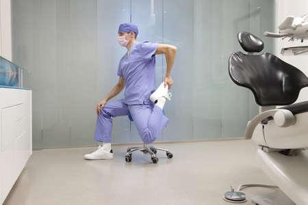 Tandarts benen uitrekken. Blanke man oefenen op tandheelkundige mobiele zadel in zijn kantoor.