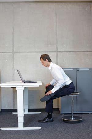 Hombre de negocios haciendo ejercicio en el asiento inclinado neumático con el portátil en el escritorio de altura ajustable eléctrica en la oficina - estiramiento en el escritorio