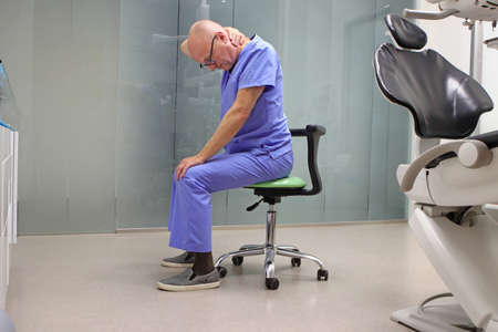 Neck pain in the dental practice.Mature dentist having short break for regeneration after long working hours in his office Standard-Bild
