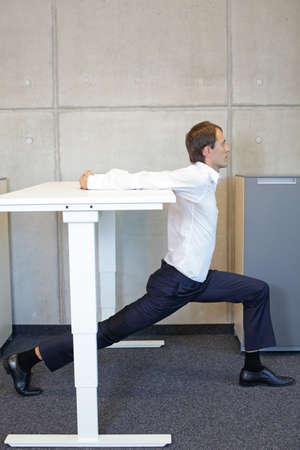 オフィスでヨガ。オフィスで電気高さ調節可能な机で運動するビジネスマン - 机でストレッチ