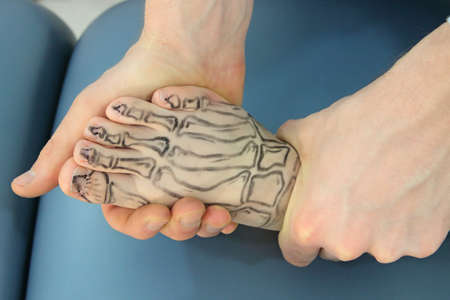 manual procedure on foot with drawing of bones on the skin