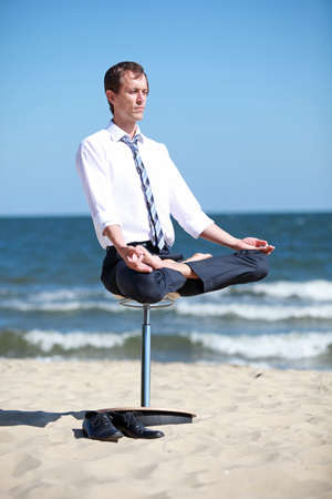 caucasian business man in lotos pose on pneumatic stool on the beach