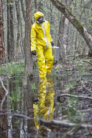 Man  in professional uniform with silver suitcase walking in contaminated floods area