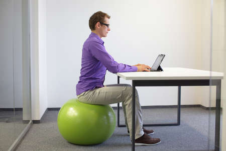 Man on stability ball working with tablet at desk in the office - correct siting posture