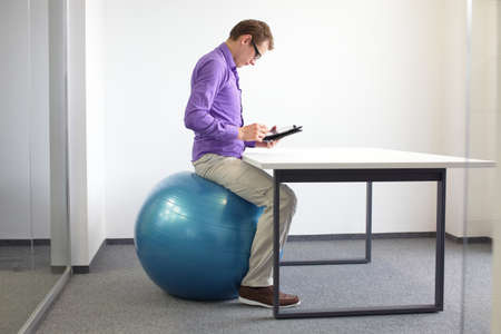 Man on stability ball working with tablet at desk in the office - changing siting position
