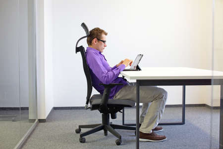 various positions sitting position at the office desk . man on chair working with tablet