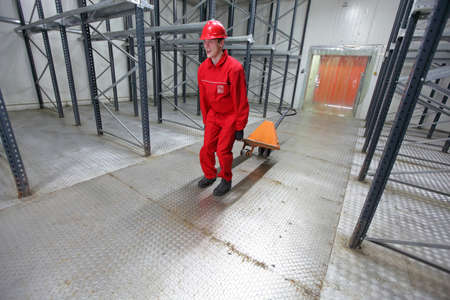 Young worker in uniform exercising with pallet truck in warehouse