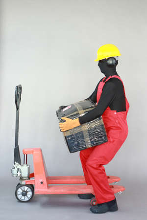 Anonymous worker lifting heavy package at manual pallet truck.Correct body position.Occupational safety and health.
