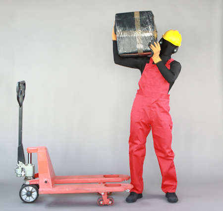 Anonymous worker carrying heavy package at manual pallet truck.Correct body position.Front view. Occupational safety and health.