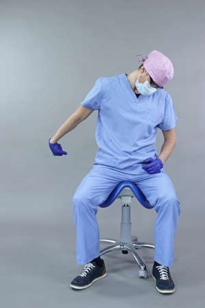 Caucasian dentist sitting on saddle doing stretching exercises for hand, arm relaxation