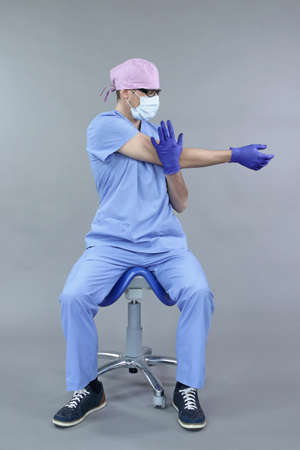 Caucasian dentist sitting on saddle doing stretching exercises for hand relaxation