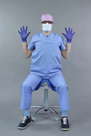 Exercise for assistant,  dentist in sitting position at chair.Caucasian man in uniform, mask and eyeglasses , stretching body   in studio - healthy lifestyle at work.