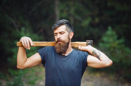 lumberjack shirt: Brutal brunette bearded man in warm hat with a hatchet in the woods on a background of trees Stock Photo