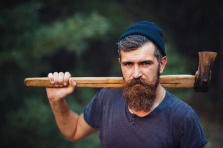 hatchet man: Brutal brunette bearded man in warm hat with a hatchet in the woods on a background of trees Stock Photo