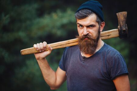 Brutal brunette bearded man in warm hat with a hatchet in the woods on a background of trees 版權商用圖片