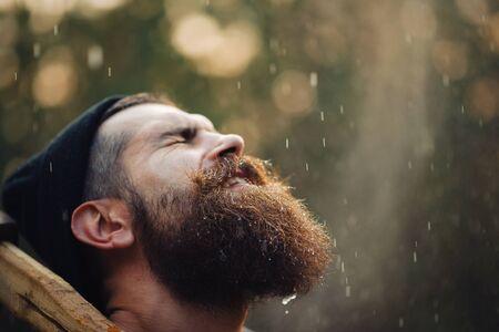 Brutal Brünette bärtiger Mann in warme Mütze mit einem Beil in den Wald auf einem Hintergrund von Bäumen
