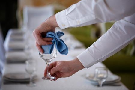 The waiter wipe glasses for wine