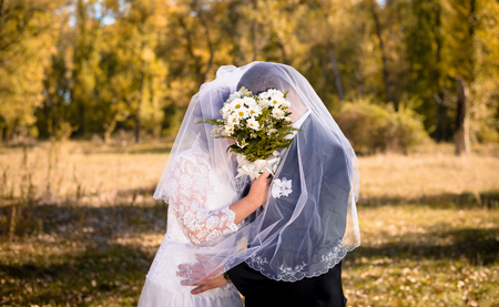 The bride with beautiful manicure closed herself and the groom with a bouquet during the kiss
