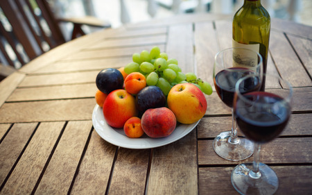 love declaration: red wine, fruit and wine on the table prepared for a romantic date Stock Photo