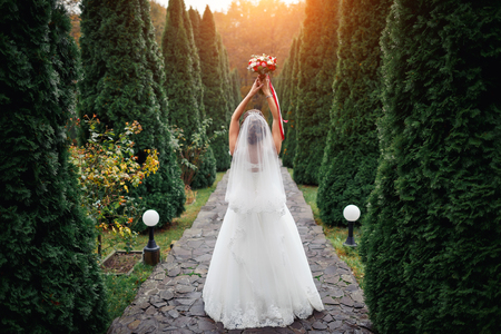 Bride in luxurious dress holding a beautiful bouquet of roses