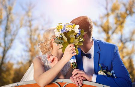 아름다운 매니큐어를 입은 신부는 키스를하는 동안 꽃다발을 들고 신랑과 신부를 닫았습니다.