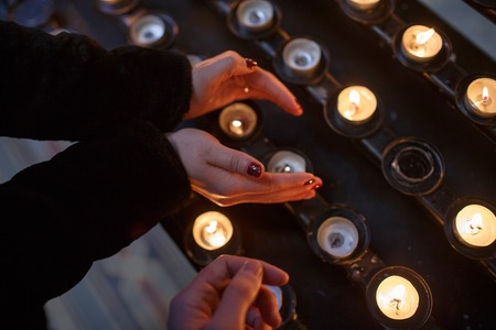 male and female hand holding a candle in church