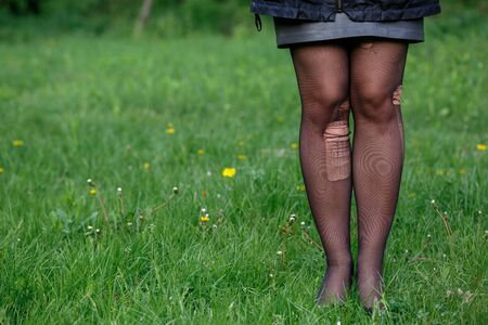 Girl legs in torn pantyhose