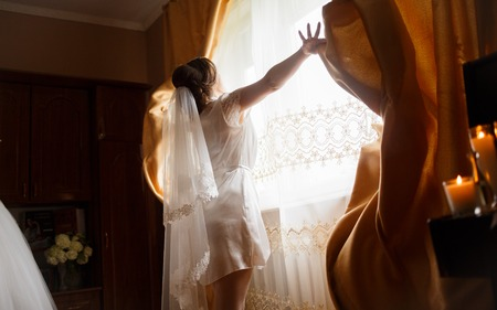 charisma: bride standing at the window and waiting for a loved one