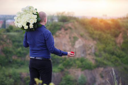 man holding a bouquet of white roses and red box with a gold ring for his girlfriend Stock Photo