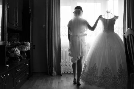 신부는 창문에 서서 사랑하는 사람을 기다리고있다. 스톡 콘텐츠